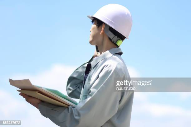 Engineer talking on smartphone with files