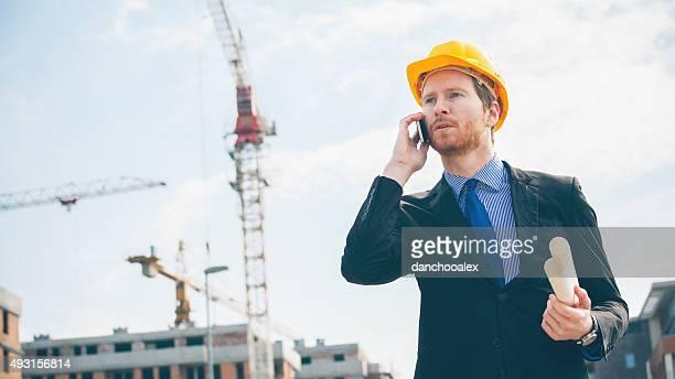 Ingenieur reden auf smart phone und hält Blau Drucken