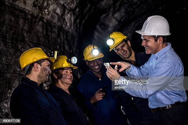 Engineer talking to a group of miners at the mine