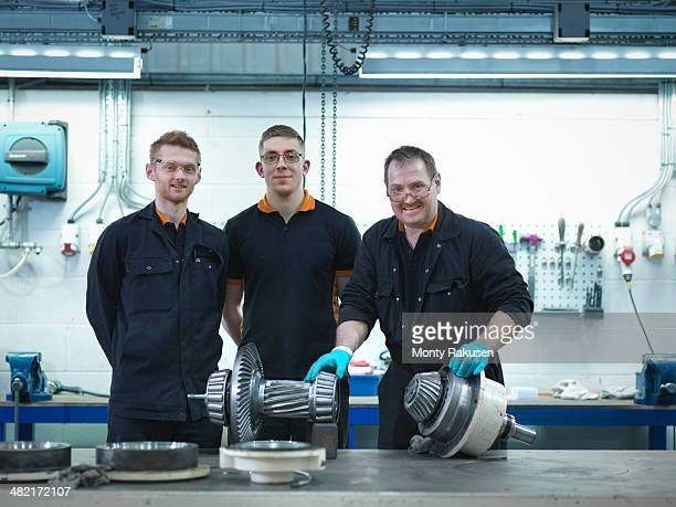 Engineer teaching apprentices in engineering factory, portrait