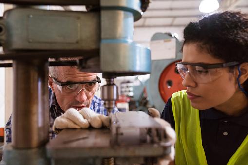 Engineer teaching female apprentice in factory 1141402967