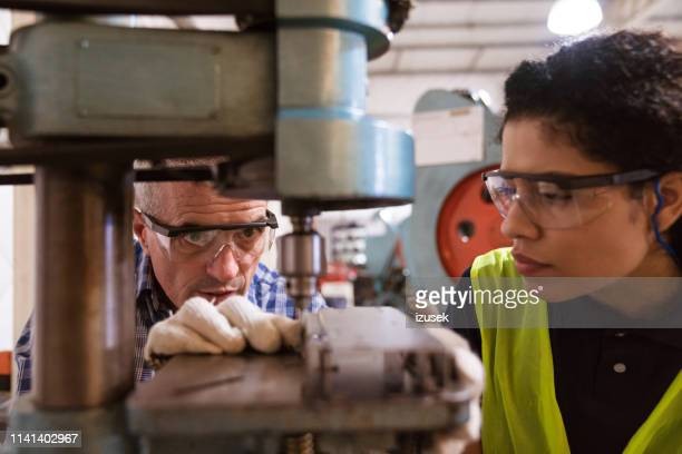 engineer teaching female apprentice in factory - teaching stock pictures, royalty-free photos & images