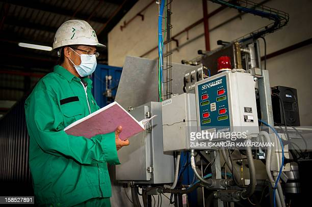Engineer / technician inspecting machine at a waste management facility