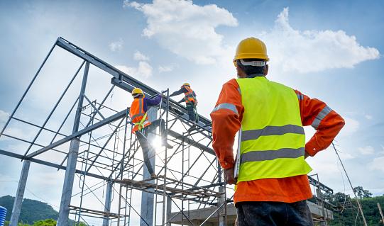 Engineer technician watching team of workers on high steel platform. 1171642478