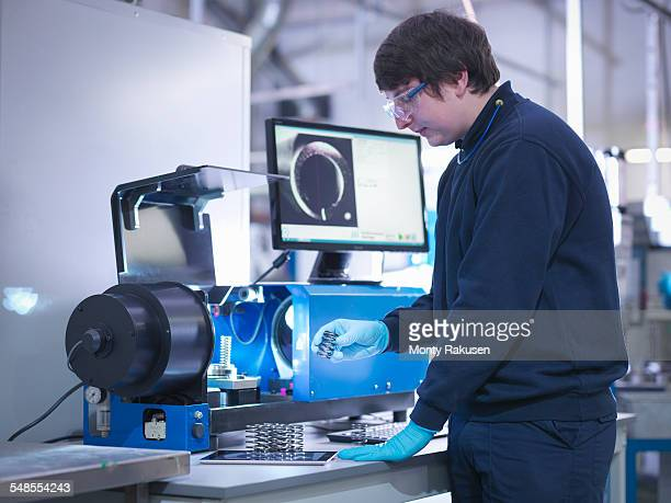 Engineer testing automotive part in factory
