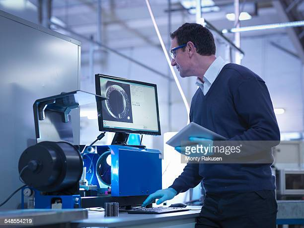 Engineer testing automotive part with digital tablet in factory