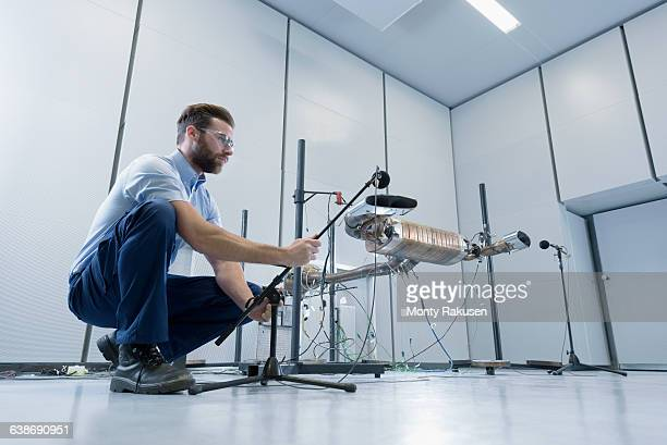 Engineer testing vehicle exhaust system in anechoic chamber