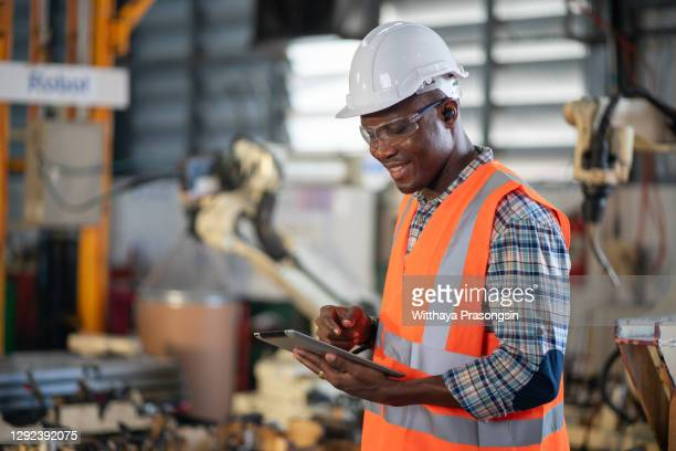 engineer touch screen control robot the production of factory parts engine manufacturing industry robots and mechanical arm - making stock pictures, royalty-free photos & images