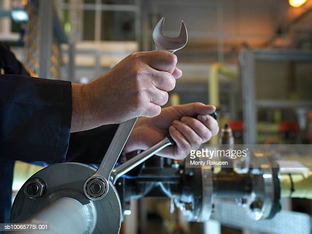 Engineer turning screws with spanner, close up of hands
