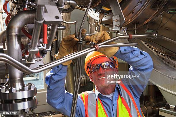 Engineer under ignitor stage of gas turbine which drives generators in power plant while turbine is powered down