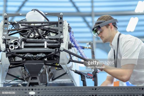Engineer using augmented reality headset to see parts position on car in assembly composite image showing CAD drawing of part in robotics research facility