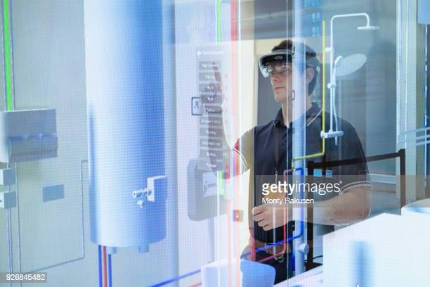 Engineer using augmented reality headset to see utilities through walls in robotics research facility