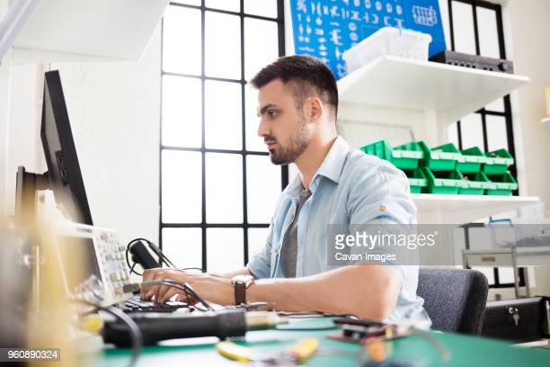 engineer using computer in electronic laboratory - oscilloscope stock pictures, royalty-free photos & images