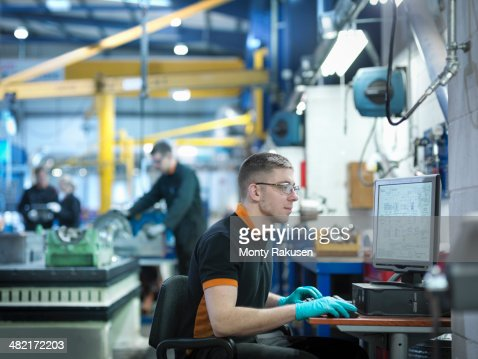 Engineer using computer in engineering factory