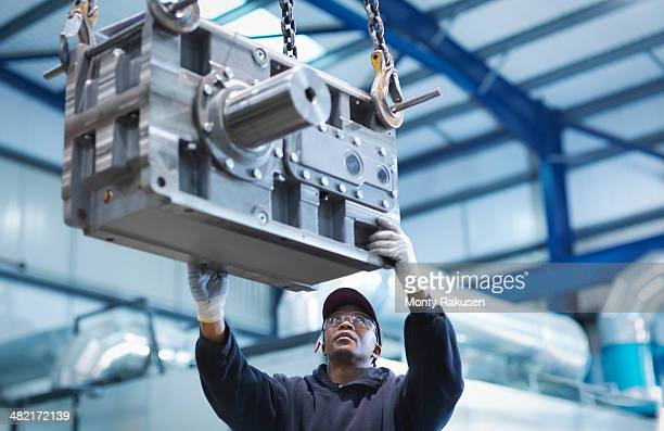 engineer using crane to move industrial gearbox to paint works in engineering factory - monty rakusen stock pictures, royalty-free photos & images