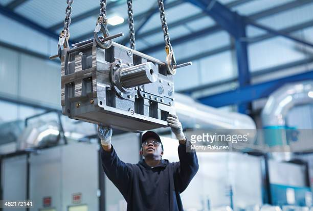 Engineer using crane to move industrial gearbox to paint works in engineering factory
