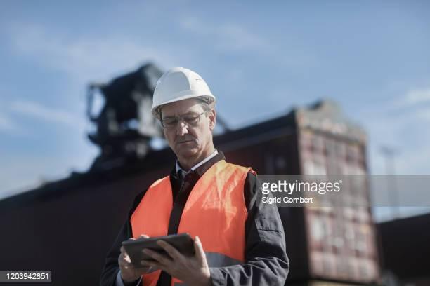 engineer using digital tablet at port - sigrid gombert stock-fotos und bilder