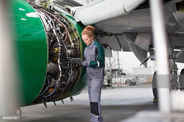 Engineer using digital tablet by airplane