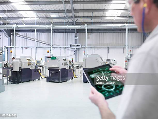 Engineer using digital tablet by production line in factory, close up