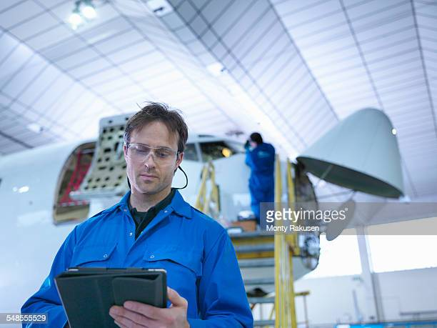 Engineer using digital tablet in aircraft maintenance factory