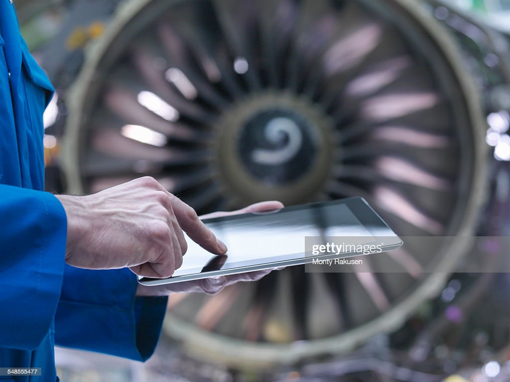 Engineer using digital tablet in front of jet engine in aircraft maintenance factory : Stock Photo