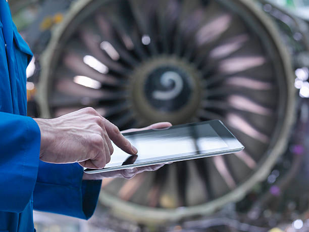 Engineer Using Digital Tablet In Front Of Jet Engine In Aircraft Maintenance Factory Wall Art
