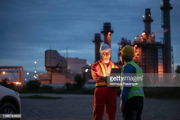 engineer using digital tablet working late night shift at petroleum oil refinery in industrial - manufacturing stock pictures, royalty-free photos & images