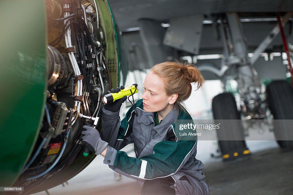 Engineer using flashlight to analyze airplane part : Stock Photo