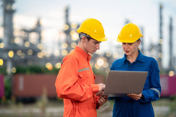 Engineer using laptop working in twilight time at petroleum oil refinery or electric plant in industrial zone.