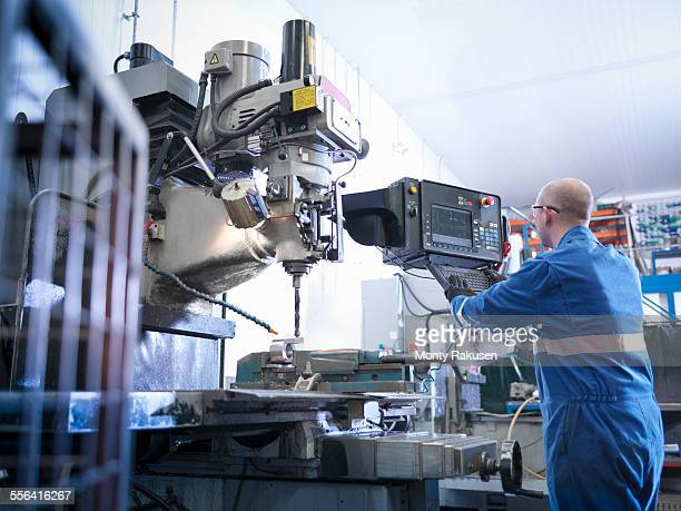Engineer using lathe in engineering factory