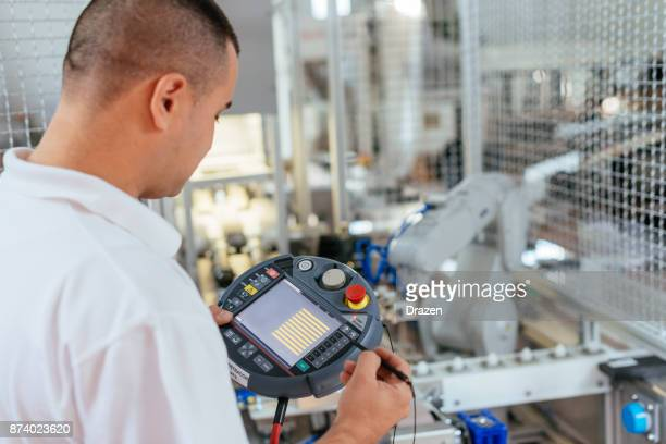 Engineer using robot pendant for production process