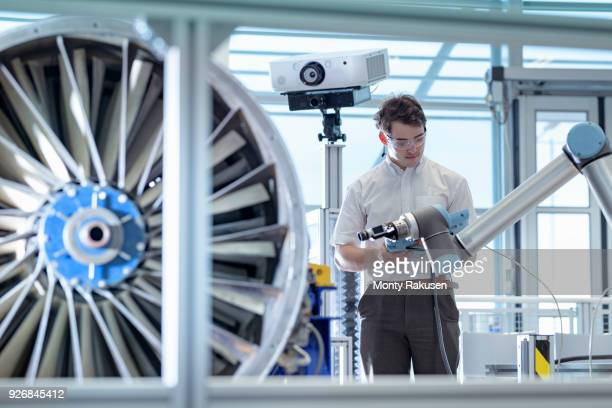 Engineer using robotic metrology to measure jet engine in robotics research facility