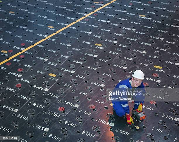 Engineer using sensors on pile cap in nuclear power station, portrait