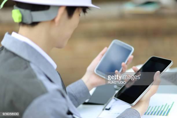 Engineer using smartphone and digital tablet on desk