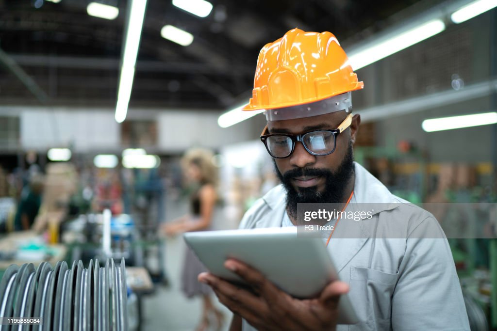 Engineer using tablet and working in factory : Stock Photo