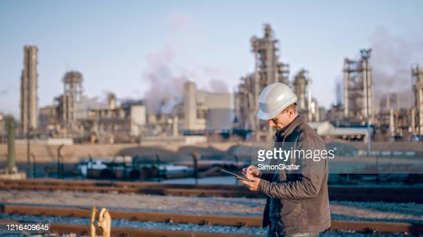engineer using tablet near oil refinery industry. - indústria petrolífera imagens e fotografias de stock