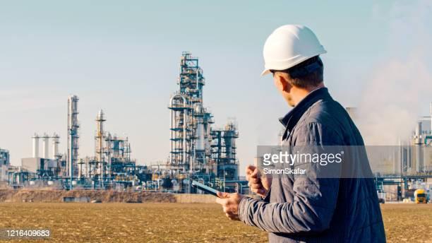 石油精製所の近くでタブレットを使用するエンジニア。 - 天然ガス ストックフォトと画像