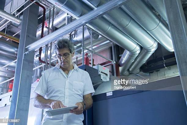 engineer using touchscreen on digital tablet in power station - sigrid gombert - fotografias e filmes do acervo