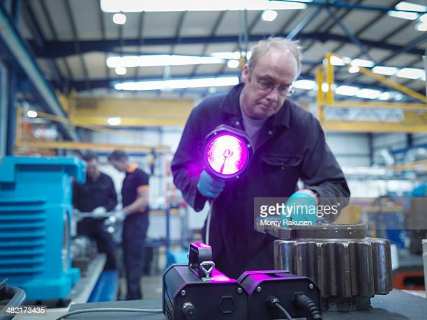Engineer using ultraviolet light to test for cracks in gear wheel