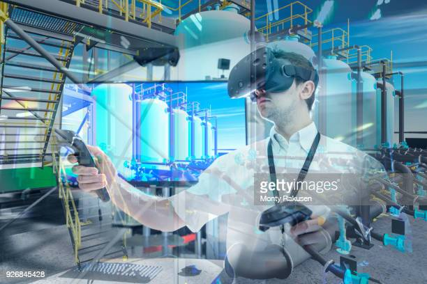 Engineer using virtual reality headset to explore 3D environment in robotics research facility
