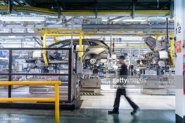 engineer walking past car production line in car factory - monty rakusen stock pictures, royalty-free photos & images