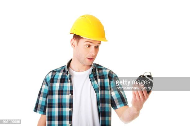 Engineer Wearing Hardhat While Standing Against White Background