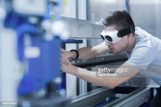 engineer, wearing safety goggles, working in engineering plant - sigrid gombert fotografías e imágenes de stock