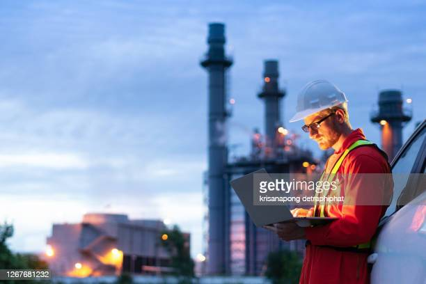 engineer wearing safety helmet using laptop with oil refinery background - industrial equipment stock pictures, royalty-free photos & images
