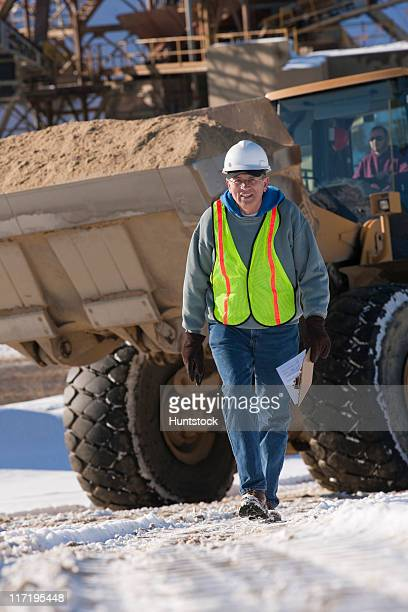 Engineer with a walkie-talkie and front end loader at a construction site
