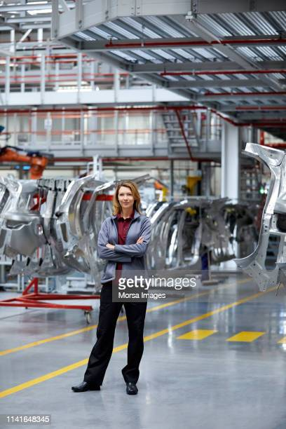 engineer with arms crossed against car chassis - manufacturing stock pictures, royalty-free photos & images