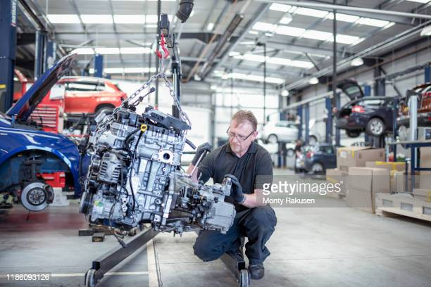 engineer with car engine in car service centre - professional occupation stock pictures, royalty-free photos & images