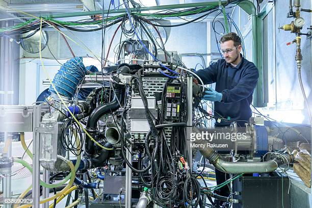 Engineer with car engine in testing bay of automotive parts factory