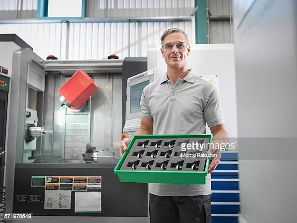 Engineer with CNC lathe holding machined products in orthopaedic factory, portrait