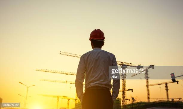engineer with crane background at sunset - built structure stock pictures, royalty-free photos & images